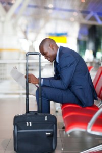 black businessman reading newspaper at airport