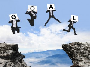 businessman jumping with GOAL text on danger precipice