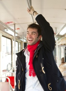 Young man smiling traveling by public transport