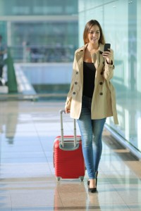 Traveler woman walking and using a smart phone in an airport
