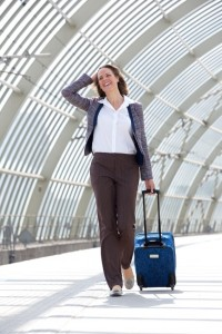 Business woman smiling and walking at station with bag
