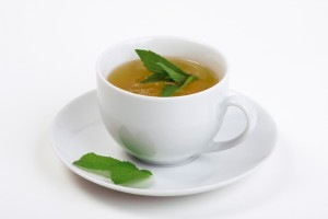 A cup of mint tea with peppermint (mint) leaves on a white background.
