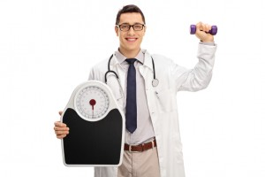 Doctor holding a weight scale and a dumbbell