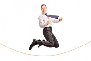 Delighted businessman jumping over a rope