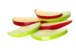 Green and red apple slices stacked on white background
