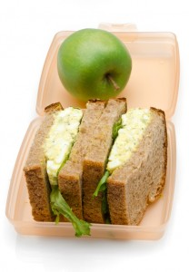 Thick egg salad sandwich with an apple