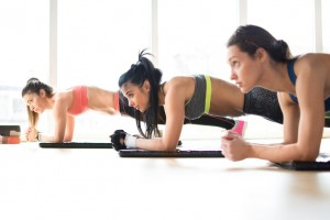Three attractive sport girls doing plank exercise in fitness class.