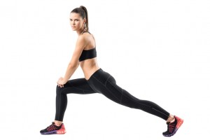 Side view of young female in sportswear doing forward lunge exercise.