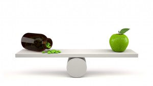 Vitamin bottle with pills and green apple on balance scales.