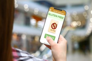 Gluten free diet concept, girl with frameless phone on blurred mall background