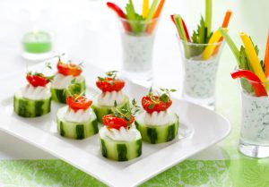 Christmas vegetable appetizers.Cucumbers with soft cheese and sun dried tomatoes and vegetable sticks with dip