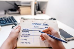 Close-up Of A Person's Hand Writing Workout Plan In Checkered Pattern Notebook. High Angle View Of A Workout Plan In Notebook At Wooden Desk