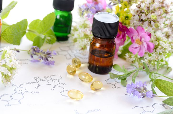 essential oils and capsules with herbs on science sheet